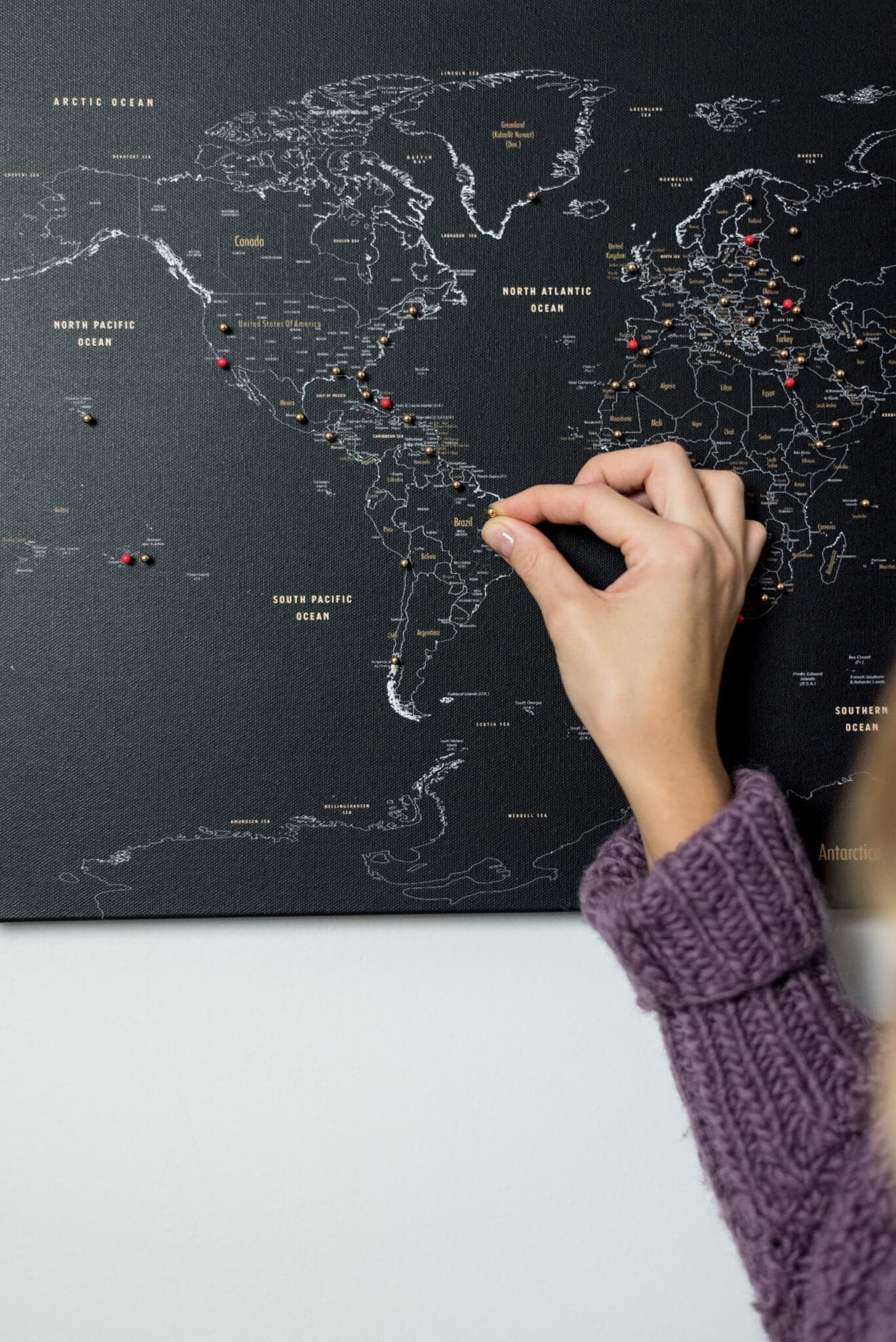 black push pin world map with golden pins